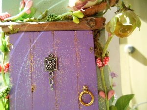 A lantern hangs above the door to light the way after dark.  A tiny silver key hangs from the peep-hole the fairies use to make sure you're not watching as they come through.